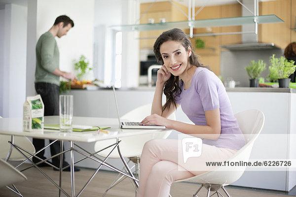 Frau  die einen Laptop benutzt  mit ihrem Mann  der das Essen im Hintergrund zubereitet.