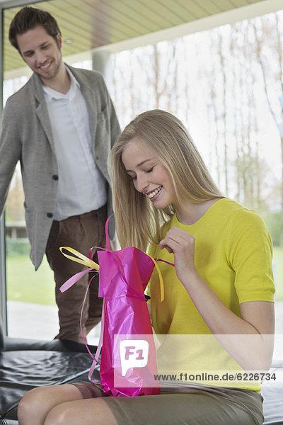 Glückliche Frau  die ein Geschenk ihres Freundes öffnet.