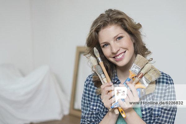 Porträt einer Frau mit Pinsel und Lächeln