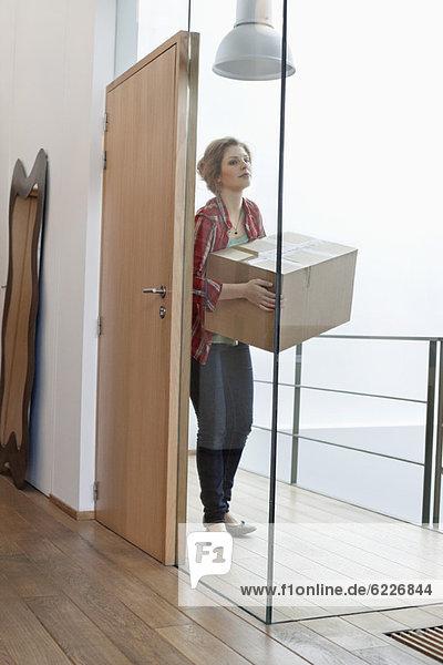 Frau mit einem Karton zu Hause