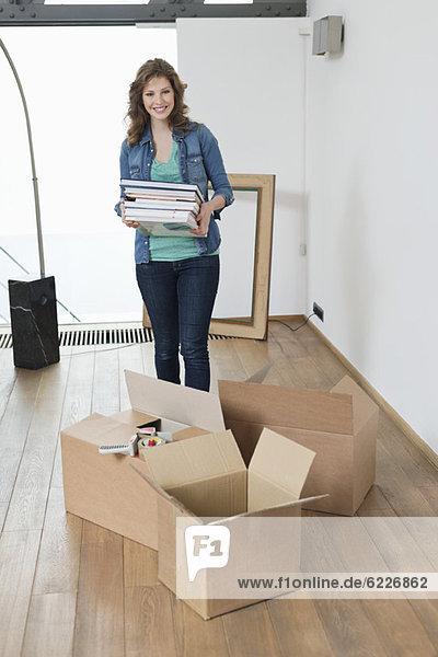 Frau mit Zeitschriftenstapel