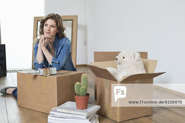 Frau stützt sich auf Karton und denkt nach