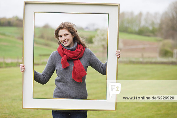 Porträt einer Frau  die mit einem Rahmen im Park steht