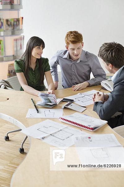 Immobilienmakler bei der Besprechung von Immobiliendokumenten für seine Kunden