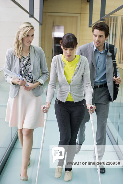Disable woman walking with business executives in an office corridor