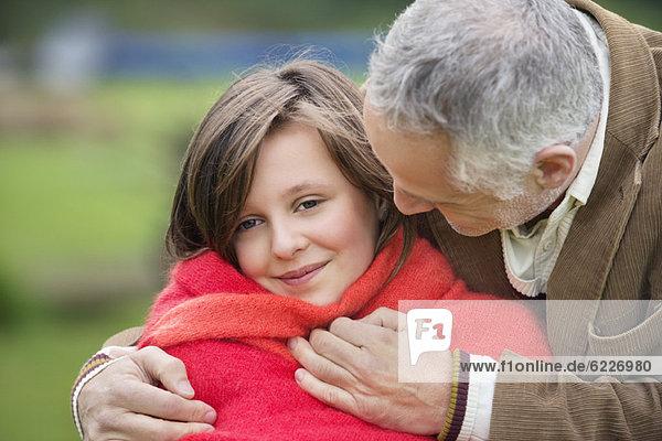 Man hugging his daughter in a park
