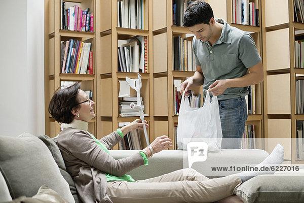 Ältere Frau auf der Couch im Gespräch mit ihrem Sohn