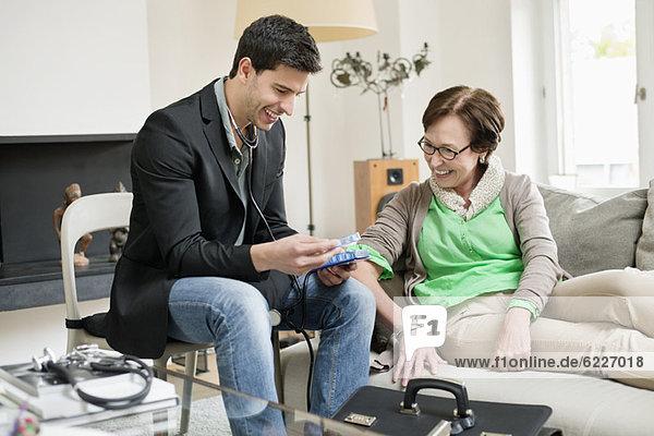 Männlicher Arzt  der einem Patienten über Medikamente aufklärt