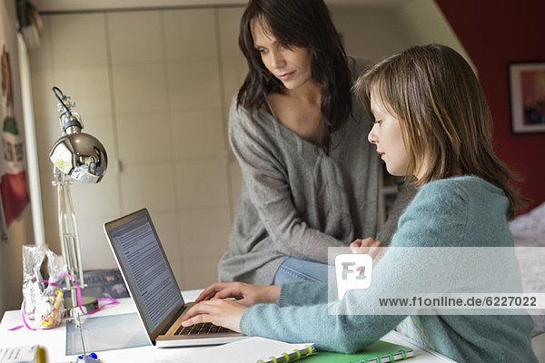 Mädchen studiert mit ihrer Mutter auf einem Laptop zu Hause