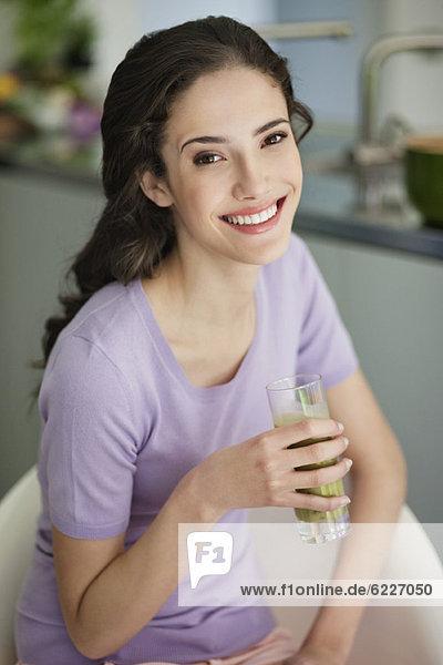Frau hält ein Glas kalte Suppe und lächelt