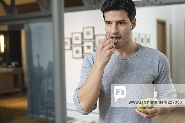 Mann isst Trauben