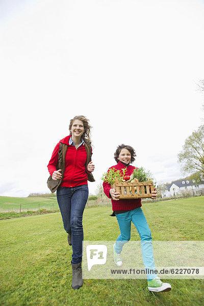 Junge trägt einen Korb mit Gemüse mit seiner Mutter auf einem Bauernhof