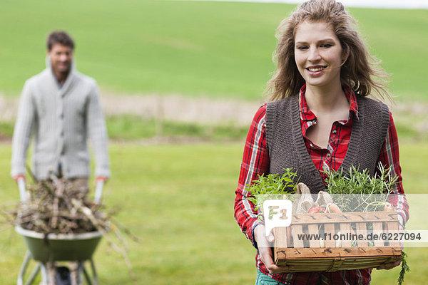 Frau hält einen Korb mit Gemüse und ihr Mann sammelt Brennholz.
