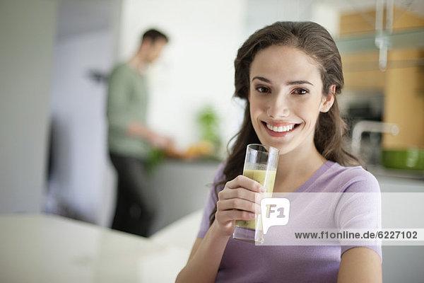 Frau trinkt Suppe mit ihrem Mann bei der Zubereitung des Essens im Hintergrund