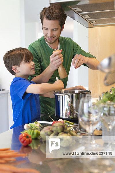 Junge assistiert seinem Vater in der Küche