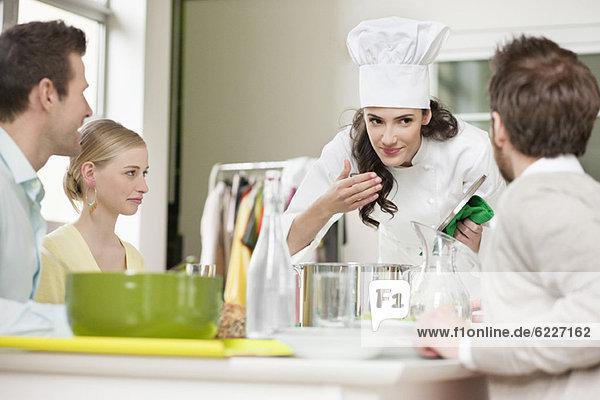 Die Köchin riecht das Essen vor dem Servieren.