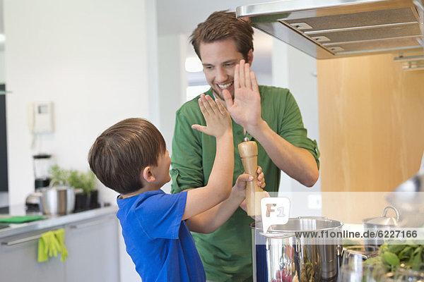 Mann und Sohn geben sich in der Küche High Five. Mann und Sohn geben sich in der Küche High Five.