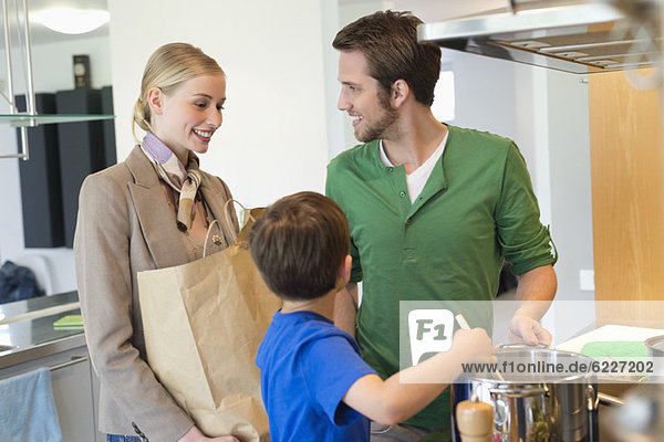 Mann und Sohn kochen Essen für Mutter vom Einkaufen zurückgekehrt