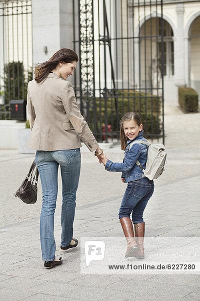 Mädchen mit ihrer Mutter auf dem Weg zur Schule