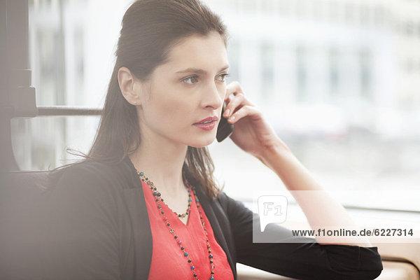 Frau reist in einem Bus und spricht auf einem Handy