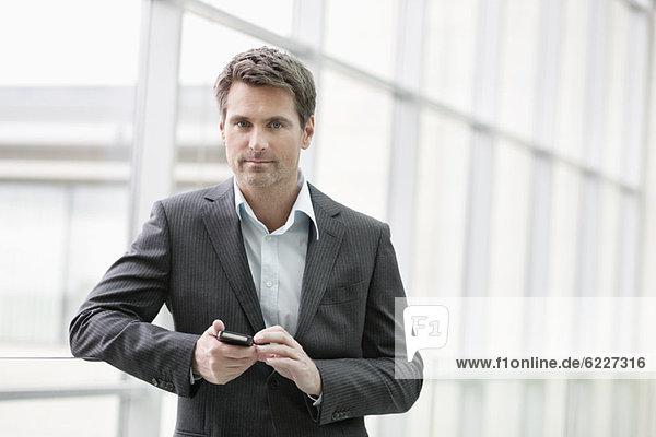 Portrait einer Geschäftsfrau SMS auf dem Handy im Büro