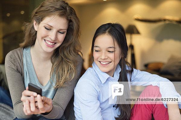 Frau mit ihrer Tochter  die ein Handy benutzt und lächelt
