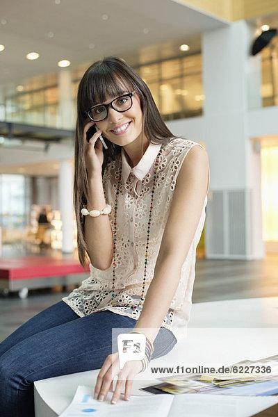 Geschäftsfrau spricht auf dem Handy und lächelt im Büro