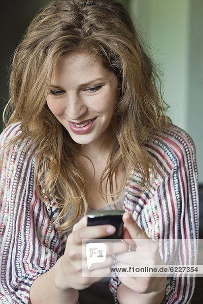 Nahaufnahme einer schönen Frau SMS auf einem Handy