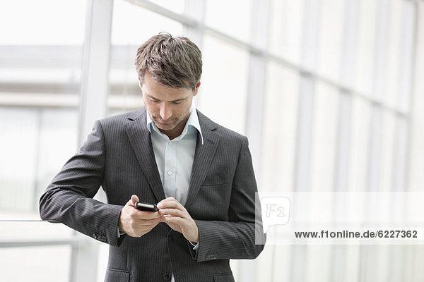 Geschäftsfrau SMS auf dem Handy im Büro