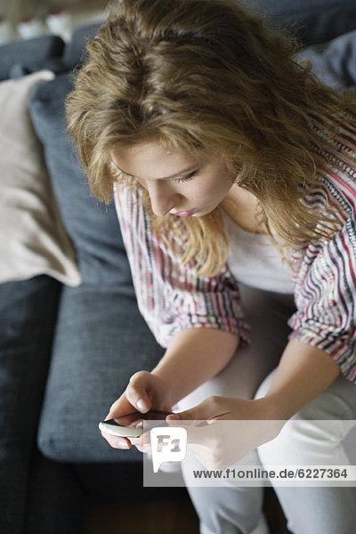 Textnachrichten von Frauen auf dem Handy zu Hause