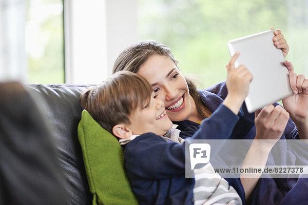 Frau mit ihrem Sohn auf ein digitales Tablett schauend und lächelnd