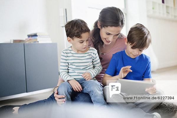Frau  die ihren Sohn mit einem digitalen Tablett ansieht.