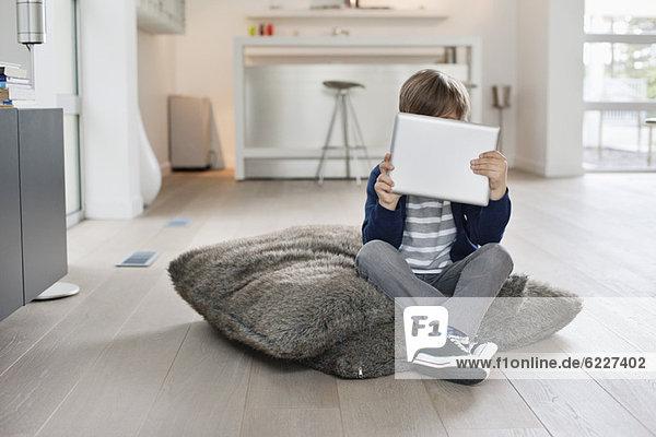 Junge  der sein Gesicht mit einem digitalen Tablett versteckt.