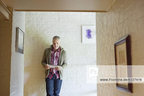 Mann mit einem digitalen Tablett in einem Flur