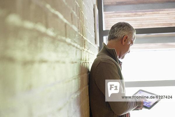 Mann mit einem digitalen Tablett in der Nähe eines Fensters