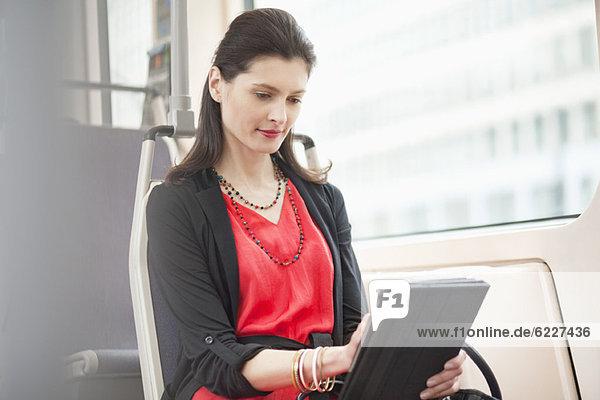 Frau  die in einem Bus mit einem digitalen Tablett reist