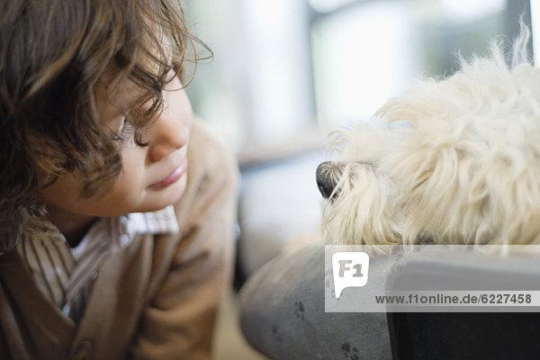 Close-up of a boy looking at a dog
