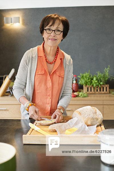 Frau beim Auftragen von Butter auf Brot