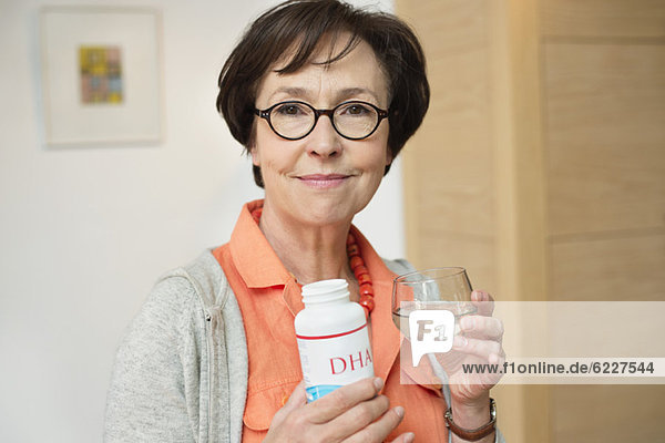 Ältere Frau hält eine Flasche Nahrungsergänzungsmittel in der Küche.