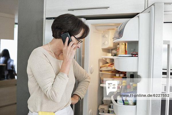 Ältere Frau schaut auf einen Kühlschrank und spricht auf einem Handy