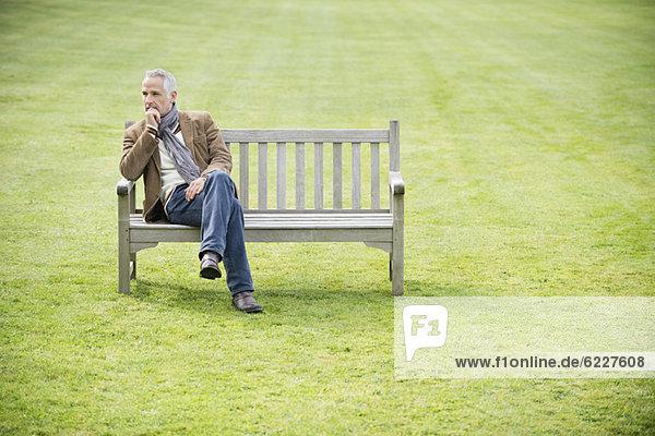 Mann sitzt auf einer Bank und denkt in einem Park