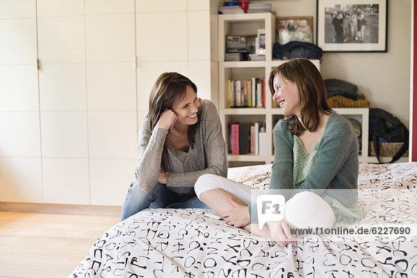 Frau mit ihrer Tochter lächelnd im Schlafzimmer