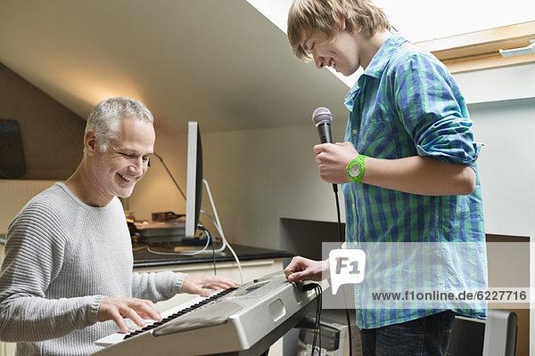 Ein Mann  der mit seinem Sohn zu Hause ein E-Piano spielt.