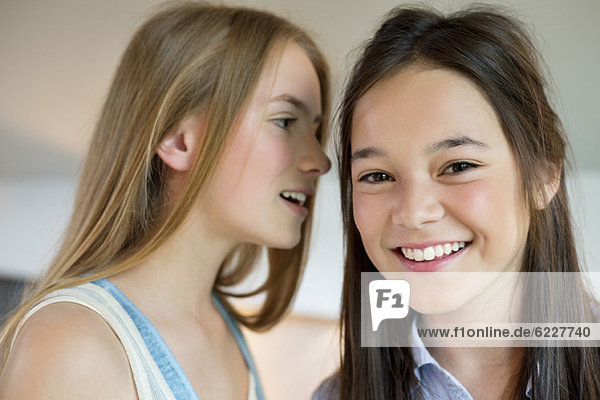 Girl whispering to her friend