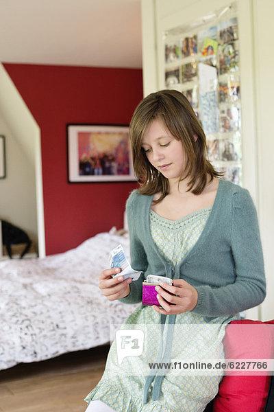 Girl holding pocket money in the bedroom