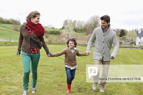 Glückliche Familie beim Spaziergang auf dem Feld