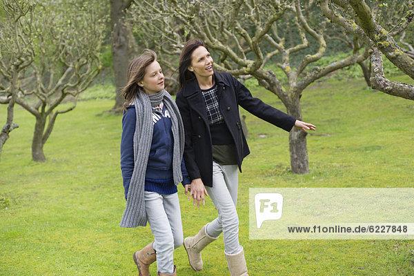 Frau mit ihrer Tochter  die in einem Obstgarten spazieren geht