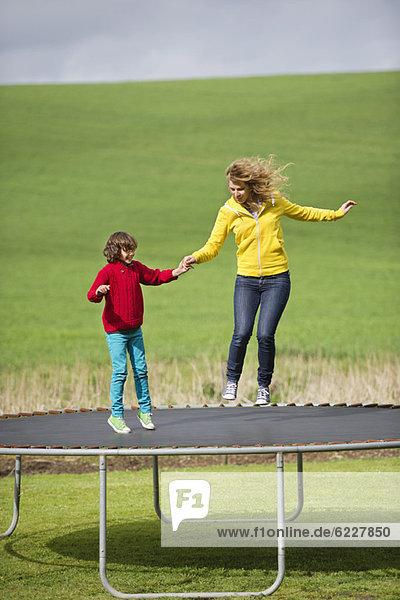 Frau mit ihrem Sohn  der auf einem Trampolin auf einem Feld springt.