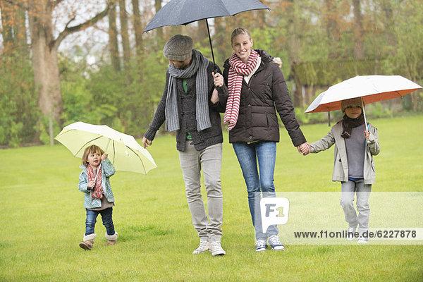 Familienwanderung mit Sonnenschirmen im Park