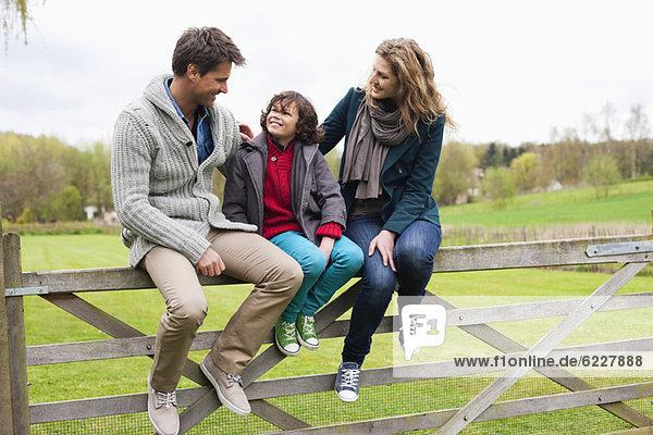 Junge sitzend mit seinen Eltern am Tor einer Hütte